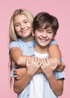 Улыбающиеся молодые братья и сестры обнимаются