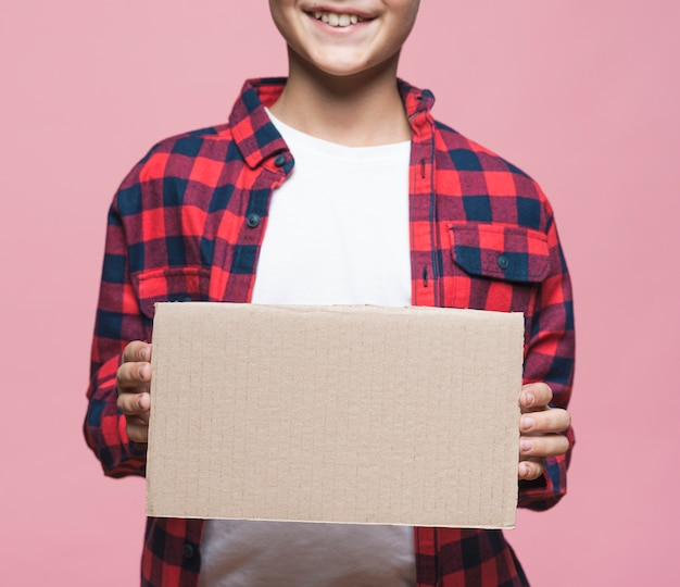 Макро мальчик держит пустой картон