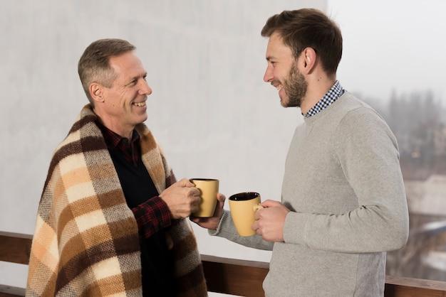 Взгляд со стороны отца и солнца усмехаясь и держа чашки в руках
