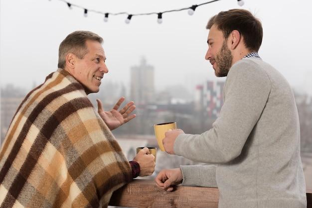 Вид сбоку отца с одеялом и сына, держа в руках чашки