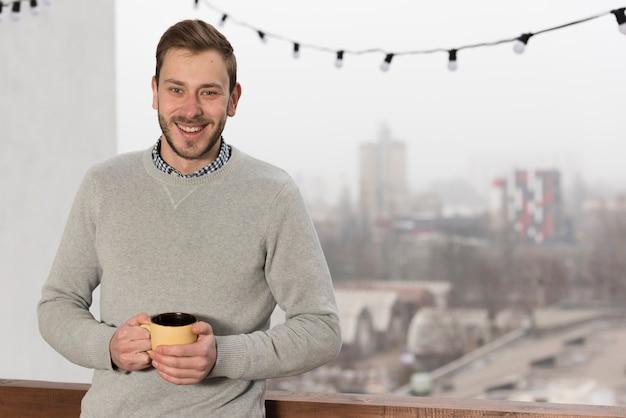 自宅でカップを保持しているセーターの男の正面図