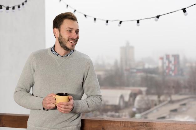 自宅の手でカップを保持しているセーターの男の正面図