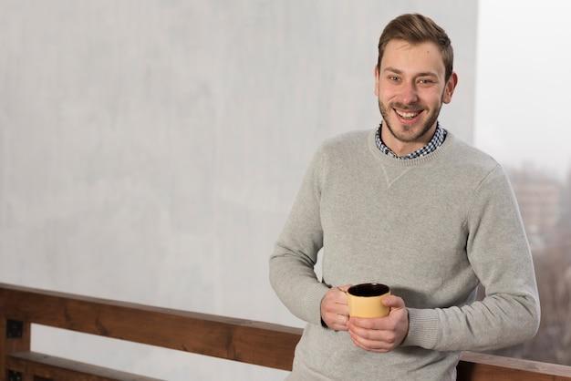 手でカップを保持しているセーターの男の正面図