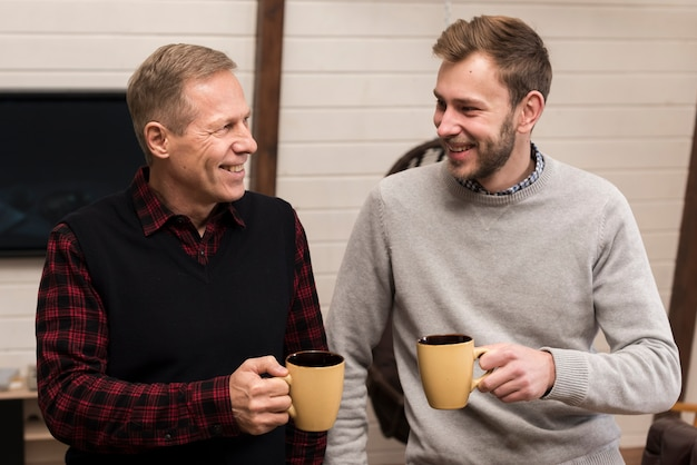 Вид спереди смайлик отец и сын позирует, держа чашки