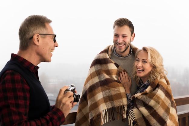 Отец фотографирует улыбающегося сына и мать