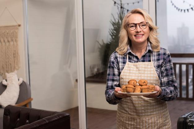 Счастливая мама с фартуком держит тарелку кексов