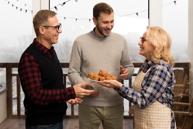 息子と父親にマフィンを与えるエプロンを持つ母