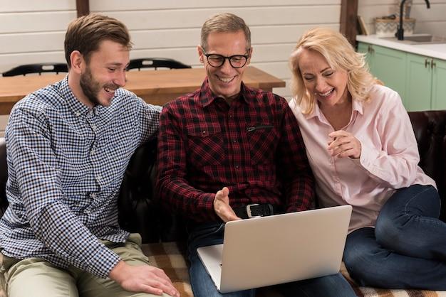 ソファの上のノートパソコンを見て家族