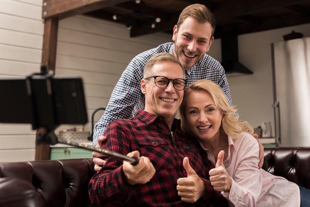 Счастливая семья, улыбаясь и принимая селфи на кухне