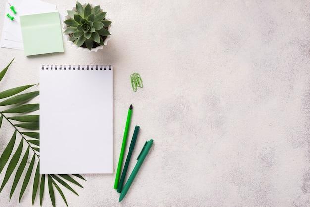 多肉植物と葉の机の上のノートブックのトップビュー