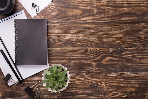 ノートブックとコピースペースを持つ木製の机の上から見る