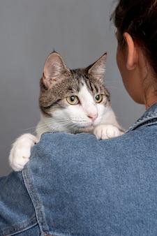 Женщина крупным планом держит кошку