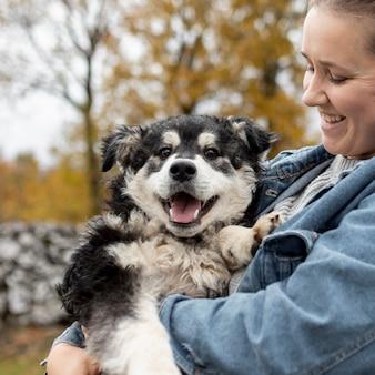 かわいい犬を保持している正面スマイリー女性