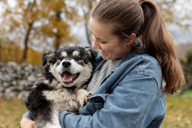 かわいい犬を保持している高角の女性