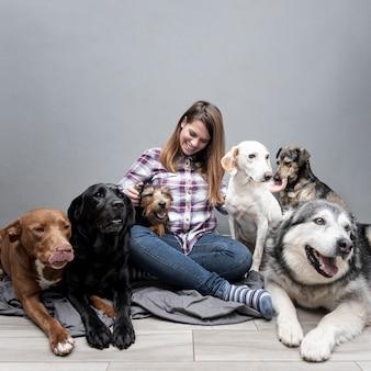 Высокий угол женщина с группой собак смешанной породы