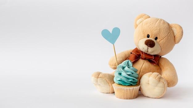 かわいい小さな男の子のカップケーキとテディベアの正面図