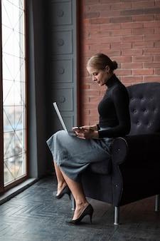 Женщина высокого угла работает на ноутбуке