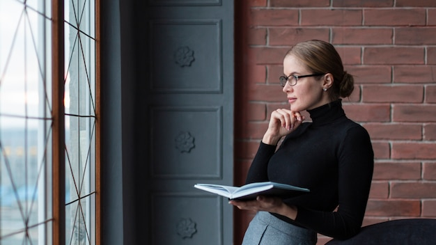 Вид сбоку женщина с книгой, глядя на окна