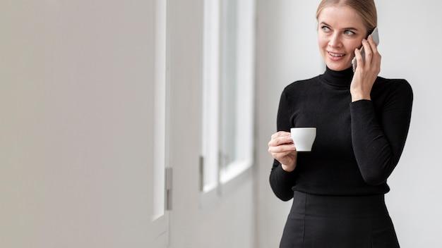 Женщина пьет кофе с копией пространства