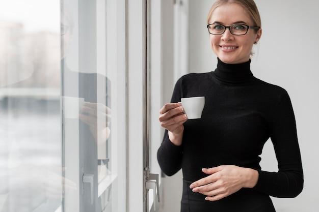 スマイリーの女性がコーヒーを飲む