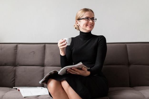 Женщина читает журнал и пьет кофе