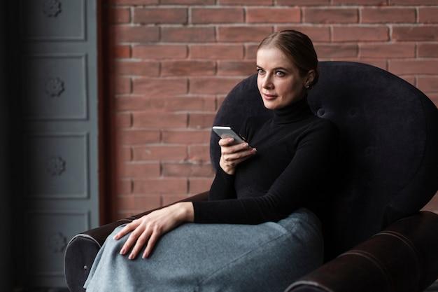 携帯電話でソファの上の女性