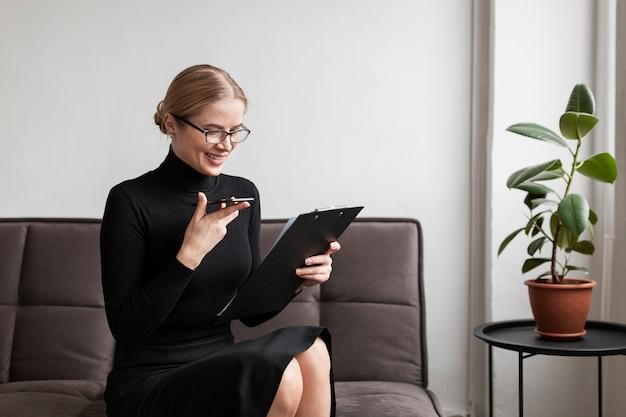 携帯電話とクリップボードを持つ女性