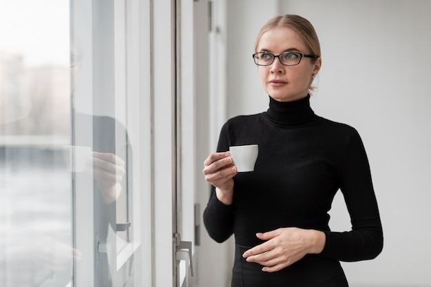コーヒーカップを持つ若い女性