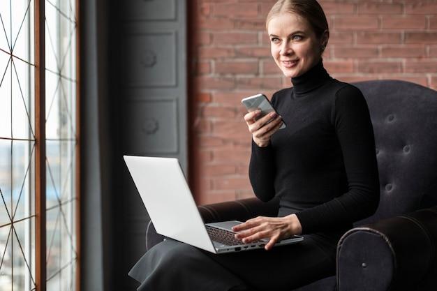 ノートパソコンと携帯電話を持つ女性