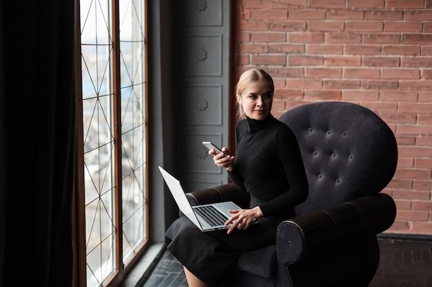 ノートパソコンと携帯電話とソファの上の高角の女性