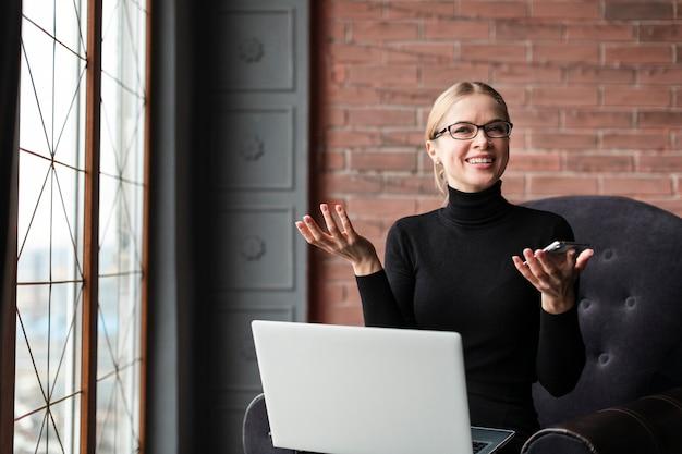 ノートパソコンと携帯電話で忙しい女性