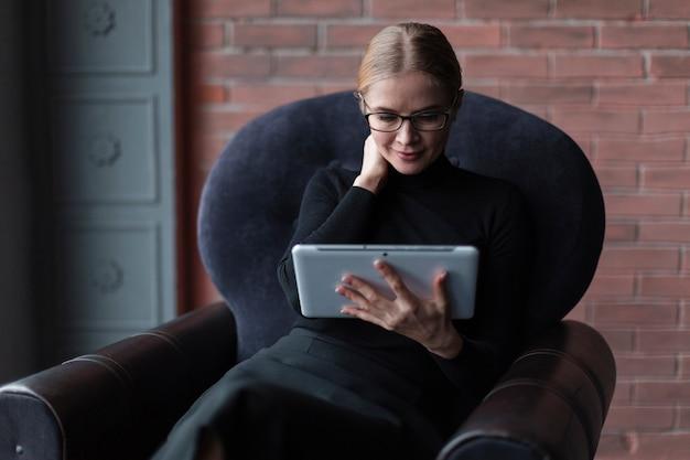 Молодая женщина с планшета на диване