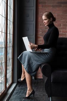 Женщина взгляда со стороны компьтер-книжки