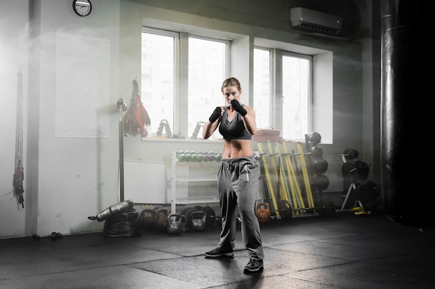ボクシングトレーニングセンターでトレーニングロングショット女性