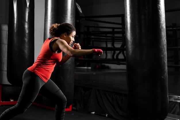 ボクシングセンターでトレーニングサイドビュー運動女性