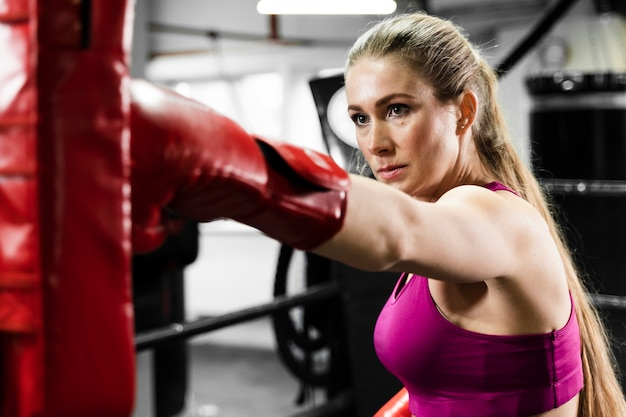 トレーニングで助けを得る運動のブロンドの女性