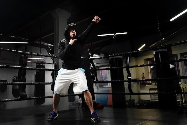 ボクシングリングでトレーニングロングショットスポーティな男