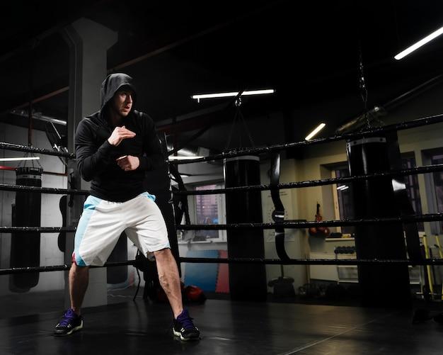 Длинный выстрел спортивного человека тренировки в боксерском ринге