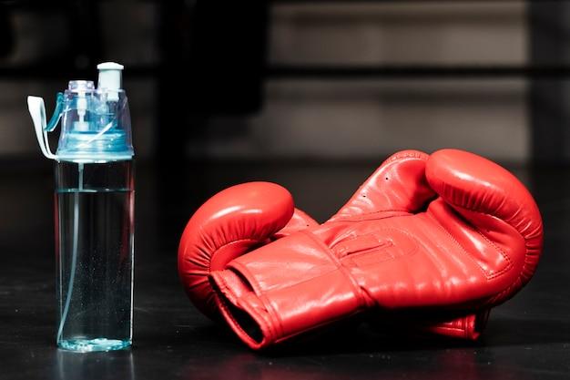 水のボトルの横にある赤いボクシンググローブのクローズアップ