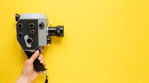コピースペースと黄色の背景に平面図ビンテージムービーカメラ