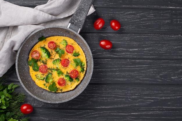 Плоская ложка кастрюли с омлетом на завтрак и помидорами