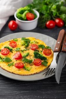 Высокий угол омлета на завтрак с помидорами и столовыми приборами