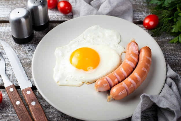 Высокий угол колбас с яйцом на завтрак на тарелку со столовыми приборами