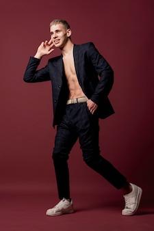 スニーカーとシャツなしのスーツでポーズをとる男性ダンサー