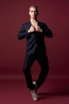 スーツとスニーカーの足を曲げながらポーズの男性パフォーマーの正面図