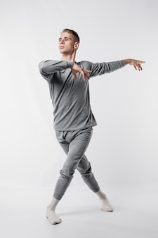 Танцовщица в спортивном костюме и носках дает позу балета