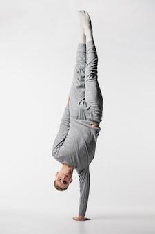 片方の腕で彼の体を持ち上げるトラックスーツの男性ダンサーの正面図