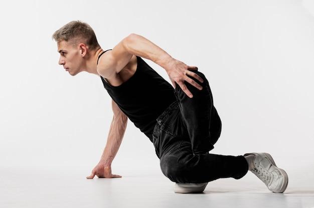 Вид сбоку танцор в джинсах и кроссовках позирует во время танца