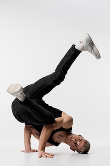 ジーンズとダンスをしながら彼の体をねじるスニーカーの男性ダンサーの正面図