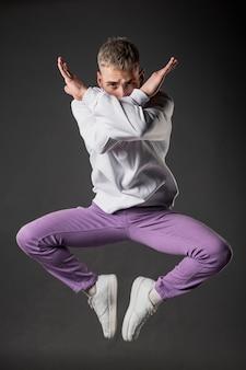 Вид спереди танцор в фиолетовых джинсах, позирует в воздухе